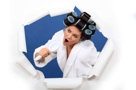Woman wearing hair rollers, singing into brush Stock Photo - 15263118