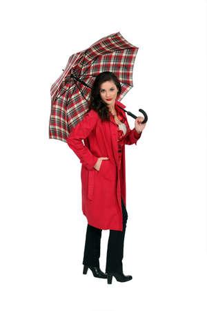 rain boots: full-length portrait of glamorous brunette holding umbrella