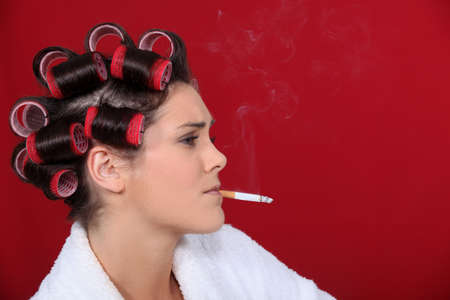 nines: woman with hair curlers against red background smoking
