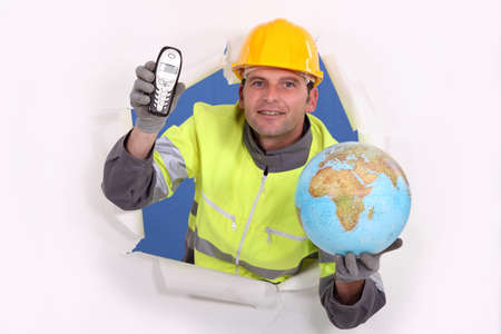 everywhere: happy-looking builder holding globe and cordless phone