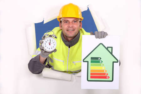 Tradesman holding an energy efficiency rating chart and an alarm clock photo