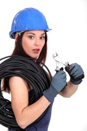 alicates: Mujer con cable el�ctrico y alicates Foto de archivo