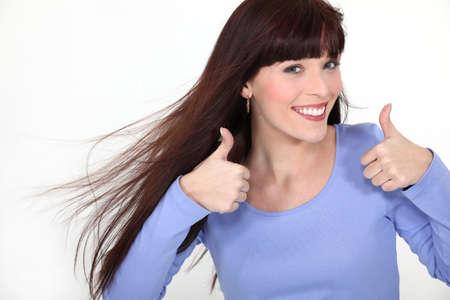 Mujer atractiva que da dos pulgares para arriba