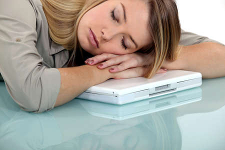 Blond woman asleep on laptop photo