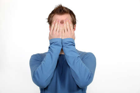 Man covering his face in shame photo