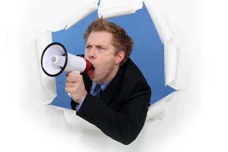 reprimanding: Businessman yelling into a blowhorn
