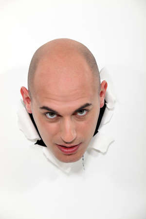 popping out: A bald man popping through a wall