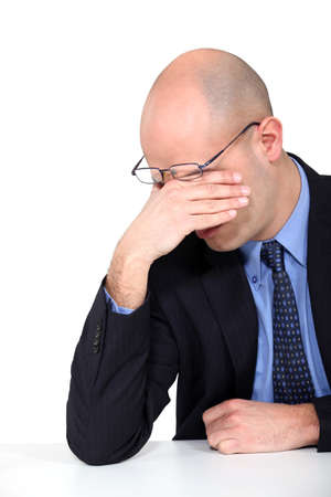 persona confundida: hombre de negocios cansado frotándose los ojos
