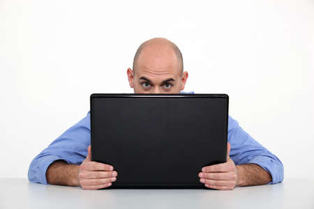 Man hiding behind his laptop photo