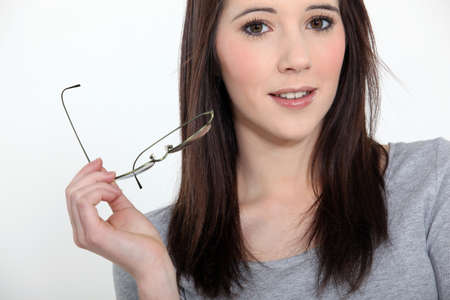 young woman taking off her glasses Stock Photo - 15263342