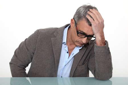 annoyance: Desperate man sitting at a desk Stock Photo