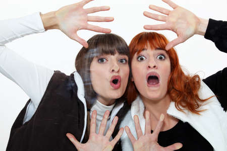 distort: Two friends pressing their face on a pane  Stock Photo