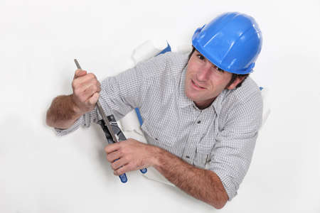 hard bound: Tradesman clasping a chisel with a pair of pliers