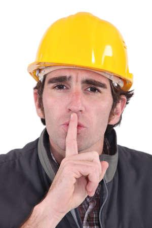 shushing: A construction worker shushing  Stock Photo