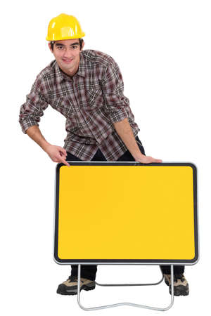 A road worker pointing at a blank sign  photo