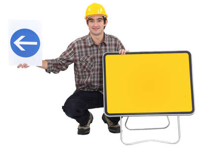 directing: Man kneeling by two traffic signs Stock Photo