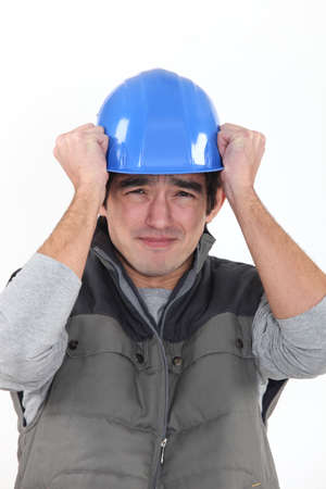 reflective background: Scared builder holding hat Stock Photo