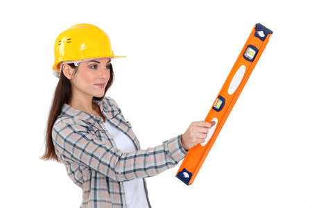 female construction worker: A female construction worker holding a level
