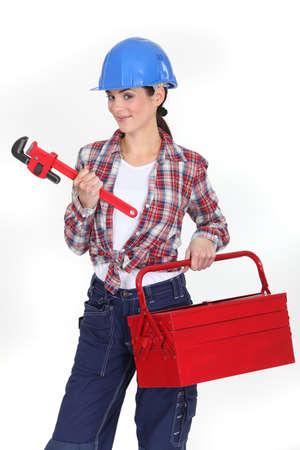 troubleshooting: Mujer con una caja de herramientas y una llave