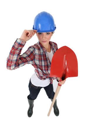 non verbal communication: Assertive tradeswoman holding a spade