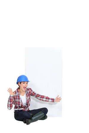 Expressive female construction worker with a blank board photo