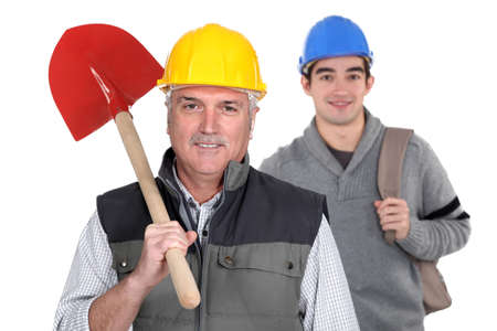 cooperative: Experienced tradesman standing in front of his apprentice