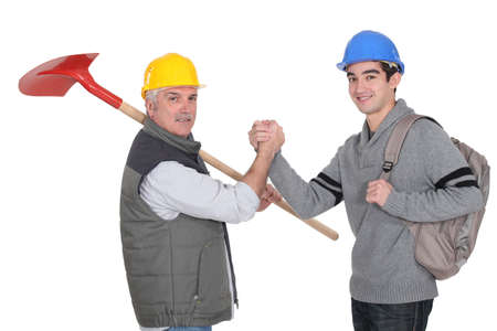 A construction worker and his apprentice shaking hands  photo