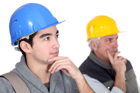 journeyman technician: Two pensive construction workers  Stock Photo