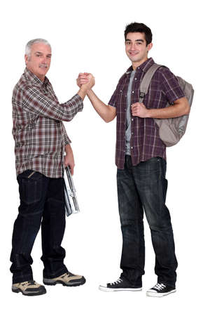 generation gap: Experienced tradesman making a pact with his new apprentice