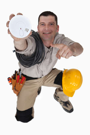 Electrician holding smoke alarm photo
