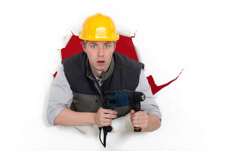 electric drill: A man popping through the wall with a drill