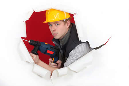 craftsman holding a drill and breaking a paper wall photo