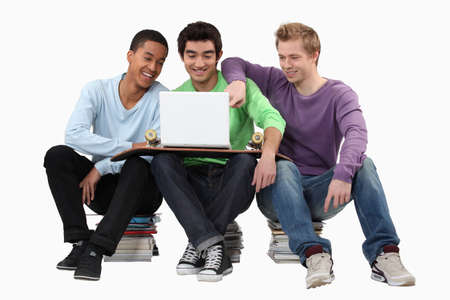 Young men looking at a laptop Stock Photo - 15263158