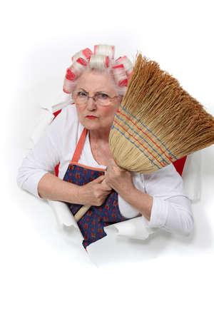 escoba: mujer enojada alto con rulos en el pelo que sostiene una escoba Foto de archivo