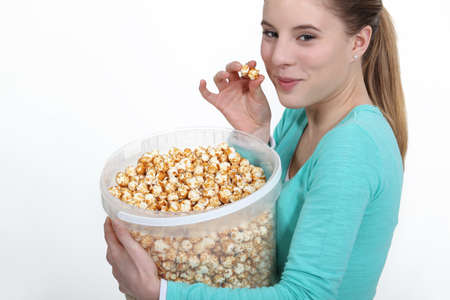 finger licking: Woman eating popcorn from large bucket