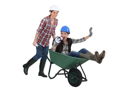pushed: Woman being pushed around in wheelbarrow Stock Photo