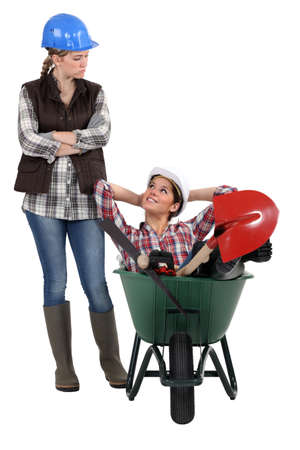 accusing: craftswoman accusing her lazy colleague for sitting in a wheelbarrow