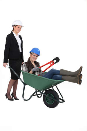 role: A professional woman pushing a blue collar worker in a wheelbarrow