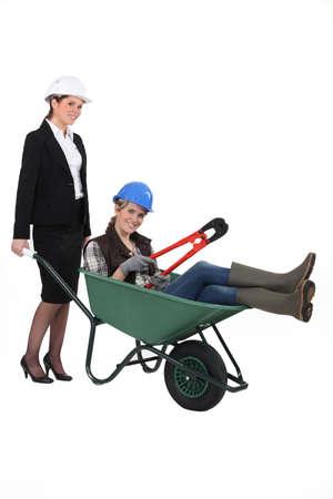 reversal: A professional woman pushing a blue collar worker in a wheelbarrow