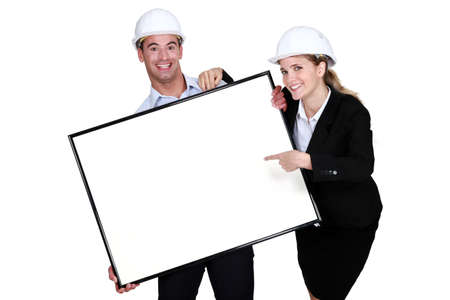 Cheerful architects with a blank board photo