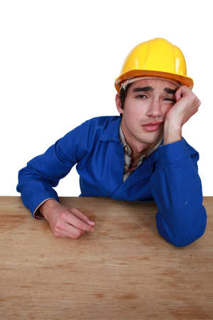 unhappy worker: young craftsman with sulky expression Stock Photo