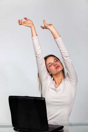 Woman with laptop stretching photo