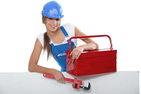 sexy construction worker: An attractive tradeswoman holding a pipe wrench and toolbox Stock Photo