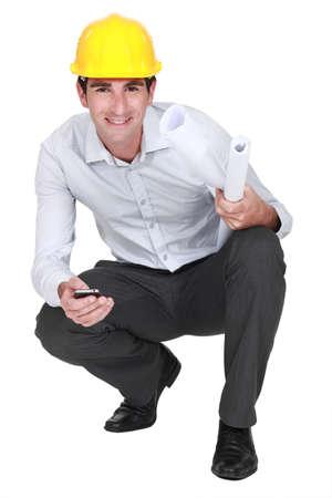 arrodillarse: Arquitecto de rodillas con el móvil y planes Foto de archivo