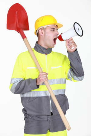 overseer: Construction with shovel shouting into megaphone Stock Photo