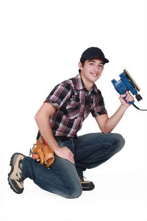 sander: portrait of young carpenter with sander machine