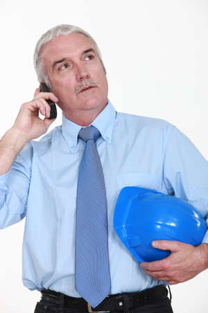 advisement: senior businessman holding a helmet and talking on his cell