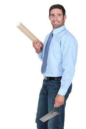 stonemasonry: Engineer holding a rolled-up plan and a trowel Stock Photo