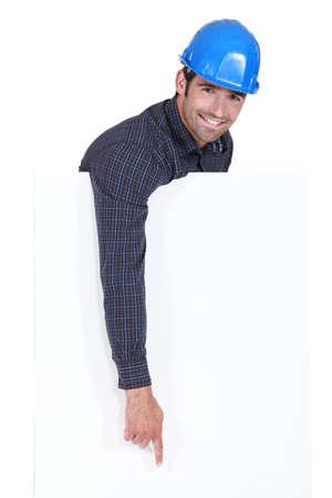 downwards: Manual worker pointing downwards at poster