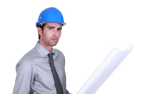 distressing: A worried engineer looking at a blueprint